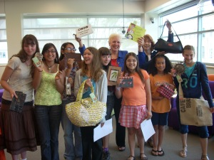 Students holding items for sale at Creative Women of the World