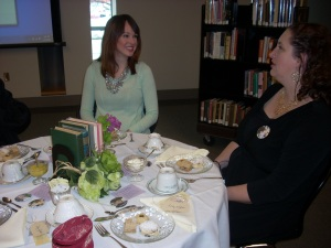 Mandy visits with a guest at our table while sitting at elegantly dressed tables adorned with pretty china dishes.