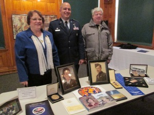 Marsha stands at her book table with 1st Lt. John Deitrick, squadron commander of Civil Air Patrol, and Marsha's brother, Mike Ringenberg.