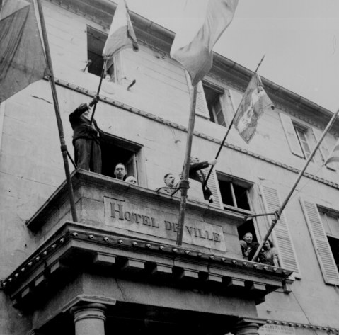 Ge Charles de Gaulle speaks to people Cherbourg from the balcony of City Hall during visit Aug 20. 1944